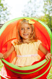 Little blond girl play and hide in toy tube Stock Images