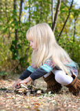Little Blond Girl Playing with Dry Sticks Royalty Free Stock Image