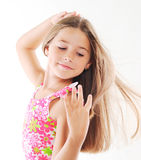 Little blond girl playing with hair. Little  blond girl with long hair. White background Royalty Free Stock Photos