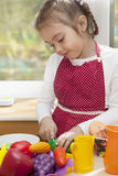 Little blond girl playing in kitchen Stock Images
