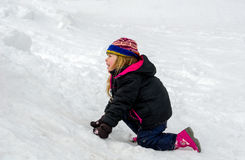 Little blond girl playing in the snow stock photos