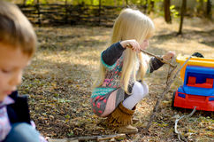 Little Blond Girl Playing Sticks on the Ground Royalty Free Stock Images