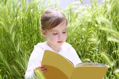 Little blond girl reading book green spikes garden Stock Photography