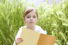 Little blond girl reading book green spikes garden Stock Images