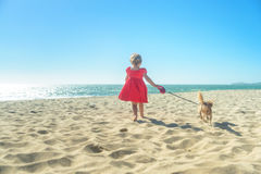 Little blond girl in red dress with dog on the beach Royalty Free Stock Images