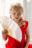 Little blond girl in red dress with fan Royalty Free Stock Photo