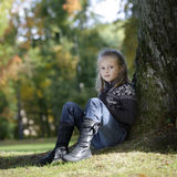 Little blond girl seated against a tree Stock Photography