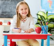 Little blond girl sit at the white desk and laughing in the school classroom royalty free stock image