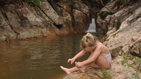 Little Blond Girl Sits Cleans Foot on Stone by Waterfall stock footage