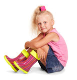 Little blond girl sitting in blouse, skirt, rubber boots . Stock Photos