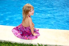 Little blond girl sitting smiling swimming pool Royalty Free Stock Photography