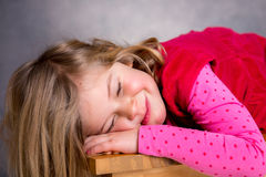 Little blond girl is sleeping. On the table Royalty Free Stock Photos