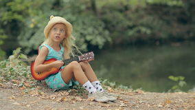 Little blond girl in a straw hat sitting near the stock video