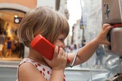 Little blond girl talking on the urban street phone Stock Photography
