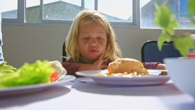 Little Blond Girl Talks at Breakfast Moves Aside Plate on Table. Little blond girl sits at white table talks eats breakfast moves aside plate by mother dish with stock video