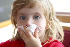 Little blond girl tissue in nose Royalty Free Stock Photos