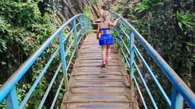 Little Blond Girl Walks along Bridge over Canyon Smiles in Park. Caucasian little blond girl with pigtail in blue walks along small bridge over canyon with stock video footage