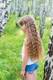 Little girl in the forest. Little blond girl with wavy hair in the forest Stock Photos