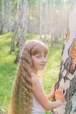 Little girl in the forest. Little blond girl with wavy hair in the forest Stock Image