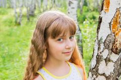 Little girl in the forest. Little blond girl with wavy hair in the forest Royalty Free Stock Photography