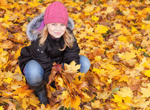 Little blond girl with yellow autumn leaves. Little blond girl seat on the park ground with yellow autumn leaves. Outdoor smiling portrait Royalty Free Stock Image