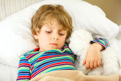 Little blond kid boy in colorful nightwear clothes sleeping Royalty Free Stock Image
