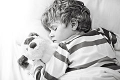 Little blond kid boy in colorful nightwear clothes sleeping Stock Images