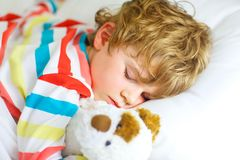 Little blond kid boy in colorful nightwear clothes sleeping Stock Photos