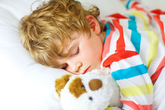 Little blond kid boy in colorful nightwear clothes sleeping Stock Photography