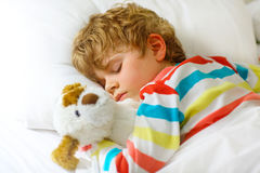 Little blond kid boy in colorful nightwear clothes sleeping Royalty Free Stock Photos