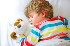 Little blond kid boy in colorful nightwear clothes sleeping Royalty Free Stock Photography