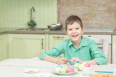 Little blond kid boy coloring eggs for Easter holiday in domestic kitchen Royalty Free Stock Image