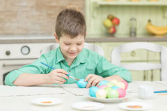 Little blond kid boy coloring eggs for Easter holiday in domestic kitchen Stock Photography