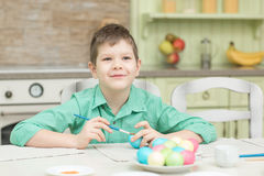 Little blond kid boy coloring eggs for Easter holiday in domestic kitchen Stock Images