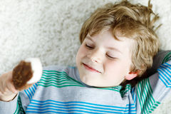 Little blond kid boy with curly hairs eating ice cream popsicle with chocolate at home Stock Photography