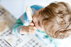 Little blond kid boy with curly hairs eating ice cream popsicle with chocolate at home Royalty Free Stock Photography