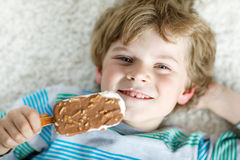 Little blond kid boy with curly hairs eating ice cream popsicle with chocolate at home Stock Photos