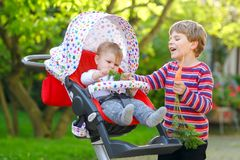 Little blond kid boy giving a carrot to baby sister. Happy siblings eating healthy snack. Baby girl sitting in pram or royalty free stock photo