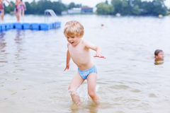 Little blond kid boy having fun with splashing in a lake, outdoo Royalty Free Stock Photos