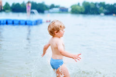 Little blond kid boy having fun with splashing in a lake, outdoo Stock Photos