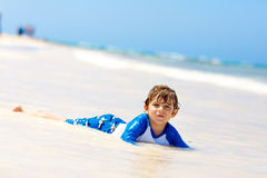 Little blond kid boy having fun on tropical beach of Jamaica Royalty Free Stock Image
