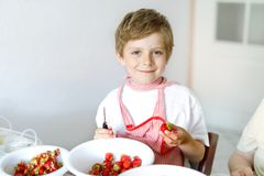 Little blond kid boy helping and making strawberry jam in summer. Funny child cleaning berries and preparing for cooking jam. Kid eating ripe strawberries in Stock Photo
