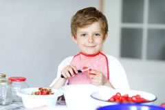 Little blond kid boy helping and making strawberry jam in summer. Funny child cleaning berries and preparing for cooking jam. Kid eating ripe strawberries in Stock Photography