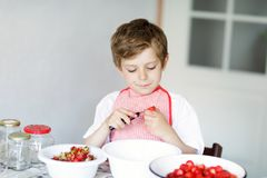 Little blond kid boy helping and making strawberry jam in summer. Funny child cleaning berries and preparing for cooking jam. Kid eating ripe strawberries in Royalty Free Stock Photography