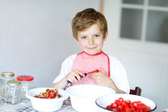 Little blond kid boy helping and making strawberry jam in summer. Funny child cleaning berries and preparing for cooking jam. Kid eating ripe strawberries in Royalty Free Stock Photo