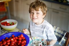Little blond kid boy helping and making strawberry jam in summer. Funny child cleaning berries and preparing for cooking jam. Kid eating ripe strawberries in Stock Photos