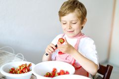 Little blond kid boy helping and making strawberry jam in summer. Funny child cleaning berries and preparing for cooking jam. Kid eating ripe strawberries in Royalty Free Stock Image