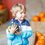 Little blond kid boy holding green pumpkin Stock Photo
