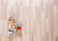 Little blond kid boy playing with colorful building blocks on floor top view. Little blond kid boy playing with colorful building blocks top view Stock Image