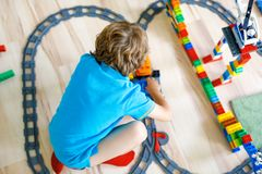 Little blond kid boy playing with colorful plastic blocks and creating train station. Adorable little blond kid boy playing with colorful plastic blocks and Stock Photo